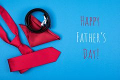 Greeting card with composition of red neck tie, pocket square and belt on blue background with inscription Happy Father`s day. Happy Father`s day greeting card stock images