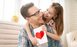 Happy father`s day. ! Child daughter congratulating dad and giving him postcard. Daddy and girl smiling and hugging. Family holiday and togetherness royalty free stock photography