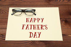 Happy Father's Day inscription with glasses on wooden background. Royalty Free Stock Photos