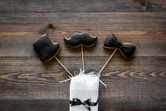 Happy father`s day morning with black tie, mustache and hat cookies, gift box for celebrate wooden background top view Stock Photography