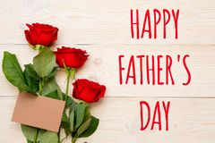 Happy father`s day, 3 red roses. With empty craft paper card on rustic table royalty free stock photos