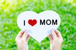 Happy Father`s day text on blur green grass background. Hand holding white heart paper with I heart MOM word on blur green grass background royalty free stock image