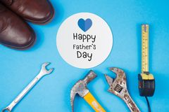 Happy Father`s Day text on card with old rusty tools and leather shoes on blue background. Happy Father`s Day text on card with old rusty tools and leather shoes stock photo