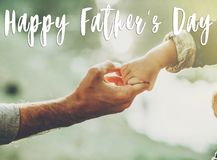 Happy father`s day text, greeting card concept. father and littl. E son holding hands in sunlight in summer forest. Trust, care and parenting family concept stock photos