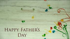 Happy Father`s Day words with small colorful heart shaped and gift boxes as background. stock image