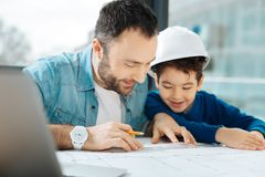Happy father showing his son how to draw a blueprint. Little lesson. Charming young architect showing his son how to draw a blueprint while the boy in a white stock images