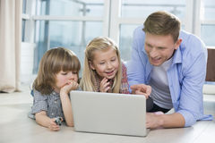 Happy father showing something to children on laptop at home Stock Images