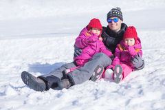 Happy father sitting in snow with his two daughters Stock Image