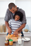 Happy father slicing bread with his son Royalty Free Stock Photo