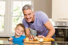 Happy father slicing bread Stock Photos