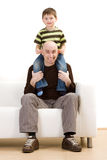 Happy father and son. Happy young boy sat on fathers shoulders on sofa, white background royalty free stock photos
