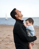 Happy father and son. Outdoor portrait of happy laughing father holding his toddler son on a beach Royalty Free Stock Photos
