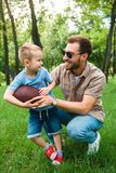 happy father and son with american football ball