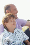 Happy Father And Son At Beach. Side view of a happy father and son sitting at on beach Royalty Free Stock Images