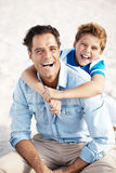 Happy father and son with big smile at the beach Stock Photos