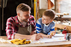 Happy father and son with blueprint at workshop. Family, carpentry, woodwork and people concept - happy father and little son with blueprint at workshop Stock Image