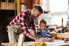 Happy father and son with blueprint at workshop Stock Photo