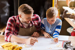 Happy father and son with blueprint at workshop. Family, carpentry, woodwork and people concept - happy father and little son with blueprint at workshop Stock Photography