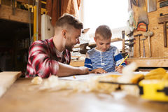 Happy father and son with blueprint at workshop Stock Image