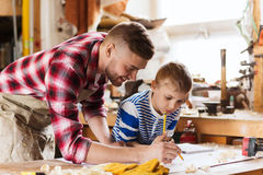 Happy father and son with blueprint at workshop. Family, carpentry, woodwork and people concept - happy father and little son with blueprint at workshop Stock Photos