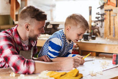 Happy father and son with blueprint at workshop. Family, carpentry, woodwork and people concept - happy father and little son with blueprint at workshop Stock Images