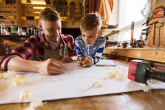 Happy father and son with blueprint at workshop. Family, carpentry, woodwork and people concept - happy father and little son with blueprint at workshop Royalty Free Stock Photo
