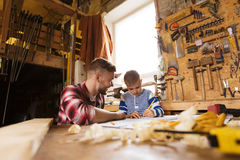 Happy father and son with blueprint at workshop. Family, carpentry, woodwork and people concept - happy father and little son with blueprint at workshop Royalty Free Stock Photography