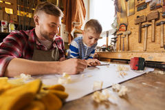 Happy father and son with blueprint at workshop. Family, carpentry, woodwork and people concept - happy father and little son with blueprint at workshop Royalty Free Stock Image