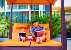 Happy father and son busy with digital tablet on vacation Royalty Free Stock Images