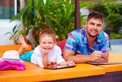 Happy father and son busy with digital tablet on vacation Royalty Free Stock Photography