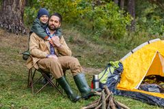 Happy father and son in camping. Happy father and son sitting in camping with tent in forest Stock Photography