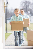Happy father and son with cardboard boxes entering new home Stock Photography