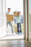 Happy father and son with cardboard boxes entering into new house Royalty Free Stock Photo