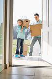 Happy father and son with cardboard boxes entering into new house Stock Image