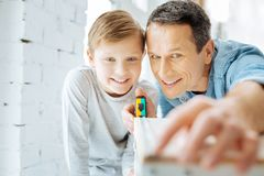 Happy father and son checking width of table Stock Photos