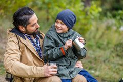 Father and son with cups. Happy father and son with cups sitting in camping in forest Royalty Free Stock Photography