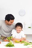 Happy father and son cutting vegetables together Stock Photography