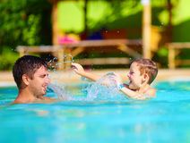 Happy father and son dabbling in pool water, summer holiday Royalty Free Stock Photography