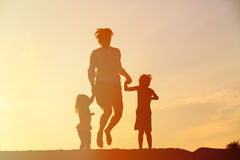 Happy father with son and daughter jumping at sunset Royalty Free Stock Image