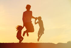 Happy father with son and daughter jumping at sunset Royalty Free Stock Photo