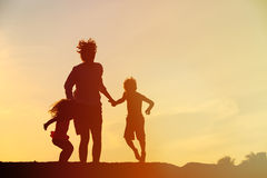 Happy father with son and daughter jumping at sunset Stock Image