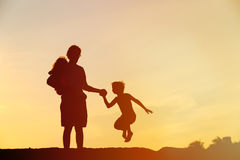 Happy father with son and daughter jumping at sunset Royalty Free Stock Photography