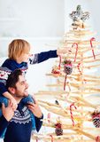 Happy father and son decorate an extraordinary christmas tree made of branches and driftwood at home Royalty Free Stock Images