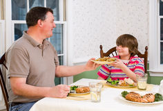 Happy father and son at dinner table Stock Photography