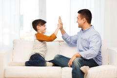 Happy father and son doing high five at home. Family, gesture, fatherhood, generation and people concept - happy father and son doing high five at home Stock Photo