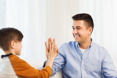 Happy father and son doing high five at home Stock Photo