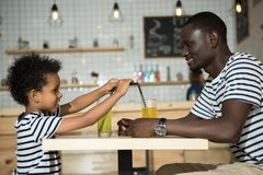 Happy father and son in cafe. Happy father and son drinking cold beverages and smiling each other in cafe Stock Photos