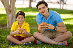 Happy father and son eating burgers royalty free stock photography