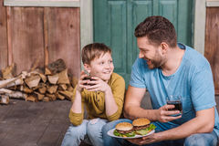 Happy father and son eating homemade burgers Stock Photo