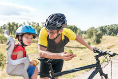 Happy father and son is eating lunch (snack) during bicycle ride. Child (boy) and men have biking helmets. The son is in the bicycle chair (seat). Caucasian Stock Images